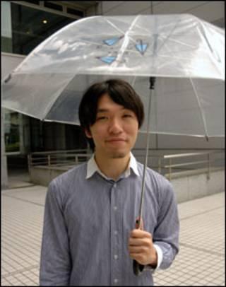 Jovem usa guarda-chuva gratuito (Foto: Ewerthon Tobace/BBC Brasil)