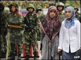 امرأتان من الويغور وفي الخلفية جنود صينيون بأورومتشي (14/07/09)