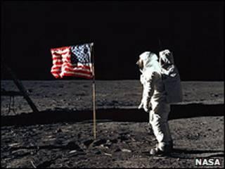 Astronauta americano na Lua, diante da bandeira dos Estados Unidos