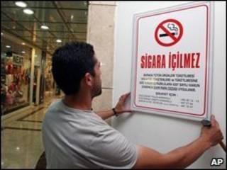 شخص يعلق لوحة كتب عليها ممنوع التدخين بإسطنبول (16/07/09)
