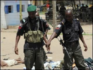Policiais nigeriano observam corpos de vítimas do conflito (AFP, 29 de julho)