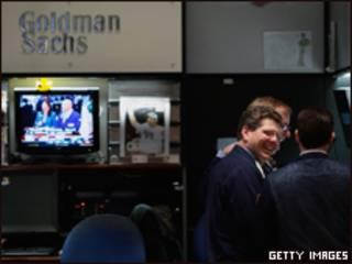 Homens riem em frente ao estande do Goldman Sachs na Bolsa de Nova York (Getty Images, 16/12/08)