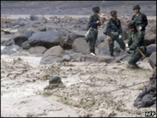 Foto liberada pelo governo de Taiwan mostra militares cruzando rio ao realizarem buscas na vila de Shiao Lin (AFP, 11 de agosto)