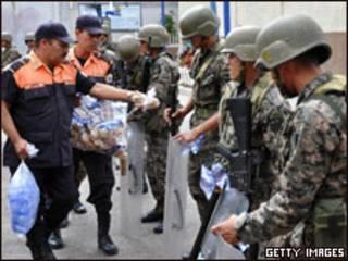 Guarda municipal distribui comida para tropas em frente à embaixada do Brasil em Tegucigalpa