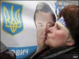 Женщина целует плакат Виктора Януковича