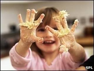 Criança com mãos sujas de lama