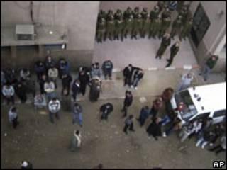 Cristianos coptos y soldados en las afueras del hospital a donde fueron llevadas las víctimas.