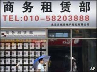 Một người dân đi qua một Đại lý bán nhà tại thủ đô Bắc Kinh