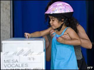 Una niña introduce el voto de su madre en una urna, en Chile