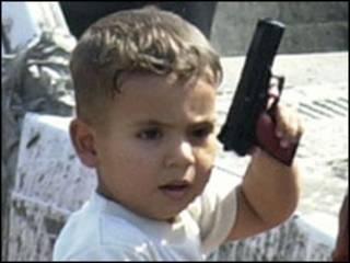 Menino segura arma de brinquedo. Foto AP/ Karim Kadim