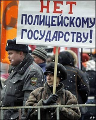 """Женщина на митинге с требованием реформ МВД держит плакат """"Нет полицейскому государству!"""""""