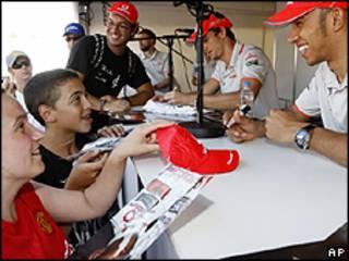 Lewis Hamilton e Jenson Button (de fundo) assinando autógrafos