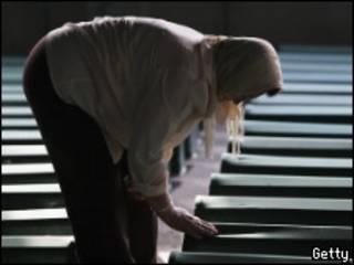 Женщина у гробов с телами жертв кровопролития в Сребренице