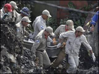 Bombeiros levam corpos no Morro do Bumba.