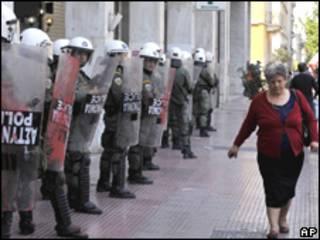 Una mujer pasa delante de la policía antimotines en Grecia