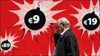 تصویری از یک مرد میانسال که از کنار پرده ای قرمز رنگ با تصاویری از بمب هایی که روی انها مبالغ مختلف یورو نگاشته شده، عبور می کند