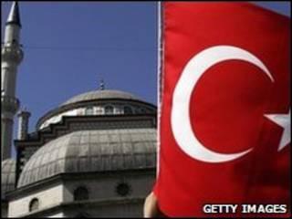 Mulher segura bandeira da Turquia em frente a uma mesquita em Istambul
