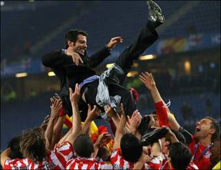 Atletico Madrid players throw their head coach Quique Sanchez Flores in the air
