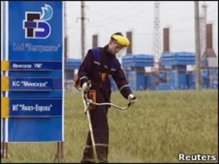 Мужчина стрижет траву у газокомпрессорной станции в Белоруссии