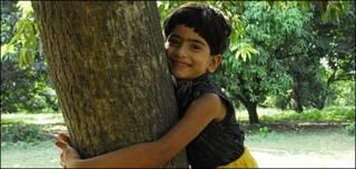 Sneha junto al mango plantado por su padre el día que nació