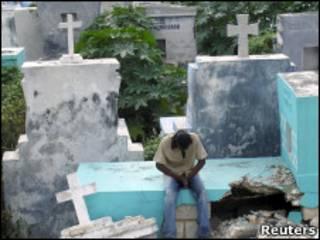 Homem reza em cemitério destruído no Haiti
