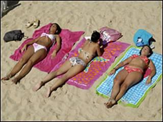 Tres chicas toman el sol en la playa