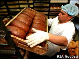 Рабочий держит поднос с хлебом