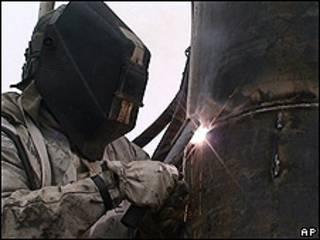 Funcionário solda tubo metálico para revestir túnel