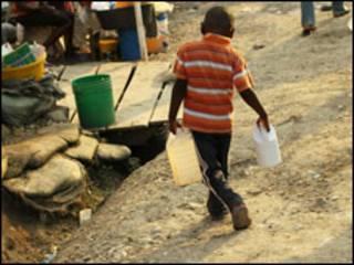 Garoto carrega água no Haiti