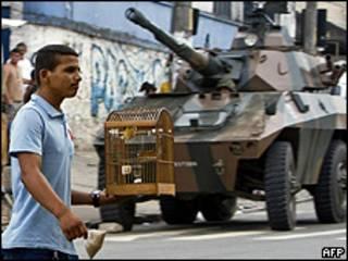 Morador passa em frente ao veículo Cascavel do Exército, no Morro do Alemão