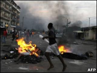 Simpatizante de Ouattara passa em frente a pneus incendiados em Abdijã