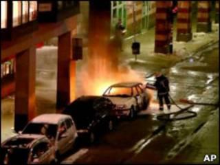 Полицейский тушит машину после взрыва
