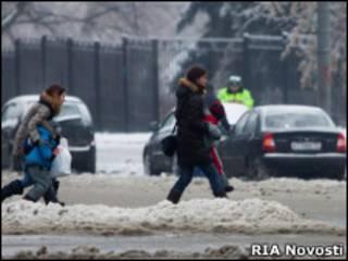 Женщины с детьми переходят дорогу