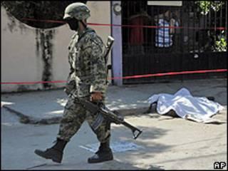 Agente junto a uno de los cadáveres decapitados hallados en Acapulco.