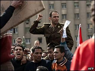 Oficial do Exército é carregado durante protesto na praça Tahrir, no Cairo (AFP)
