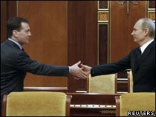 Дмитрий Медведев и Владимир Путин пожимают руки друг другу