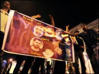 Manifestantes xiitas exibem cartaz com rostos de pessoas detidas durante manifestação na cidade de Awwamiya, no dia 3 de março, de 2011.