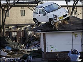 Homem fotografa danos causados pelo terremoto em Sendai (AP)