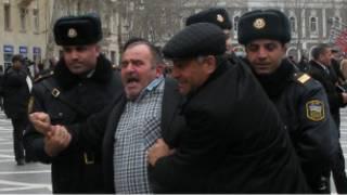 Участника акции протеста ведут за руки полицейские