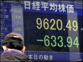 Homem passa por anúncio luminoso da Bolsa de Tóquio, que teve dia de queda