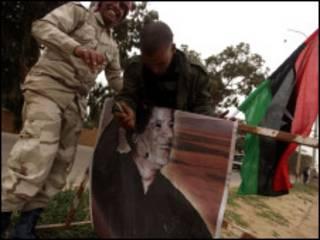 Rebeldes que partiram de cidade atacada violam imagem de Khadafi no caminho rumo a Benghazi