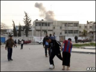 Palestinos jogam bola na Faixa de Gaza durante ataque israelense