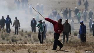Un manifestante lanza piedras contra la policía en Bolivia.