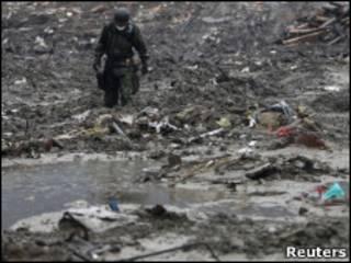Soldado japonês faz busca em área devastada pelo terremoto e pelo tsunami