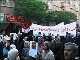 Foto feita por manifestante com telefone celular mostra mulheres levando faixa onde se lê: 'As mulheres de Deraa querem um fim ao cerco' (AP)