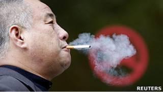 """Курильщик в Шанхае напротив надписи """"курить запрещено"""""""