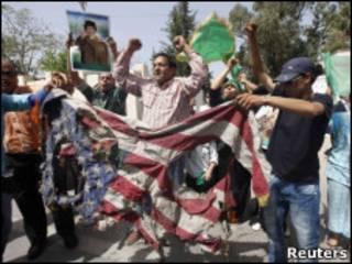 Partidários de Khadafi queimam a bandeira americana em Trípoli.