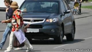 Два пешеходных переходят дорогу перед машиной