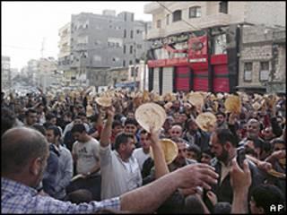 Imagem feita com telefone de celular de manifestante mostra protesto na cidade de Baniyas, no qual manifestantes mostravam pedaços de pão (AP)
