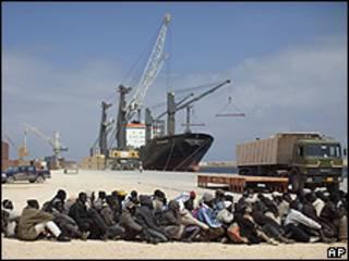 Trabalhadores imigrantes esperam transporte depois de chegar no porto de Benghazi, vindos de Misrata (AP)